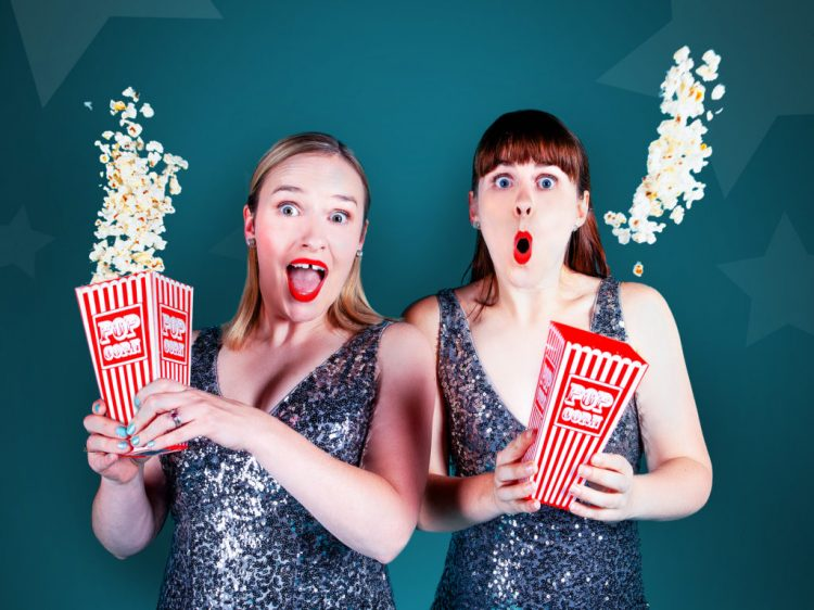 two women in silver dresses and holding popcorn