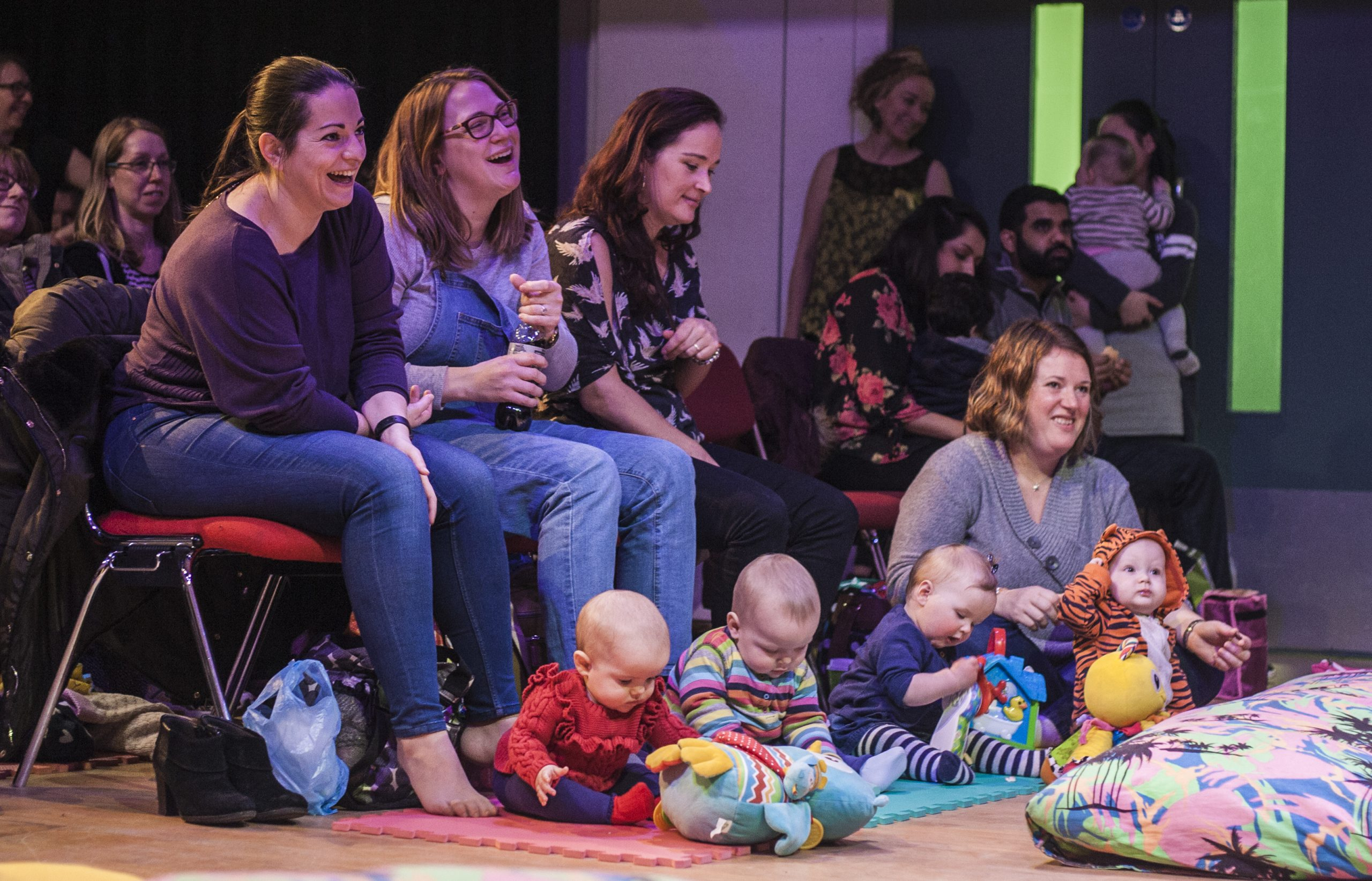 mothers and babies laughing at a comedian