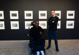 a man standing next to an artist in a wheelchair at his exhibition