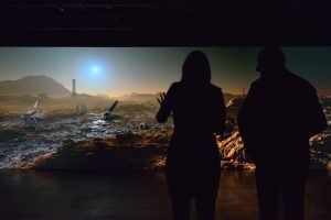 a couple silhouetted in front of a mars landscape