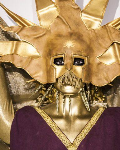 A golden clad dummy wearing a golden sun mask