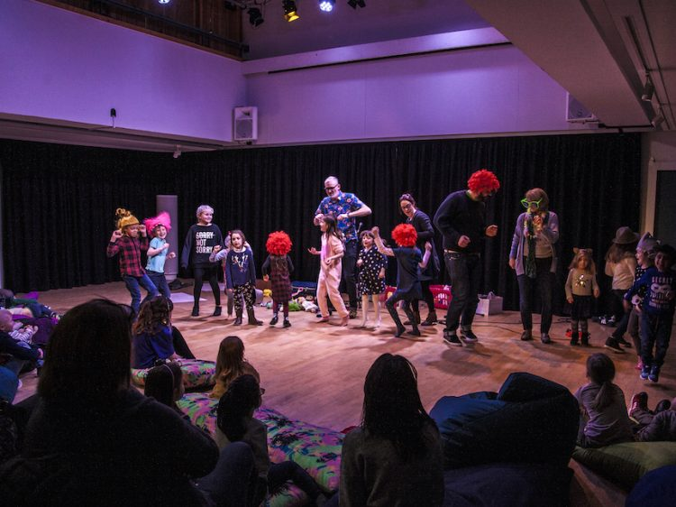 a group of children and adults being silly on stage