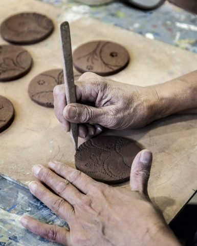 close up of hands etching clay discs