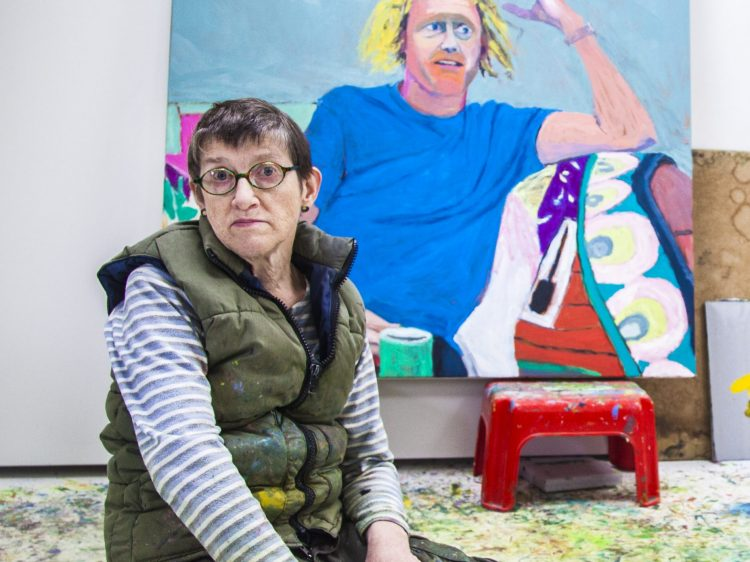 A female artist kneeling in front of a portrait
