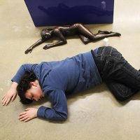 a bronze statue sprawled on the ground, with a person copying the layout