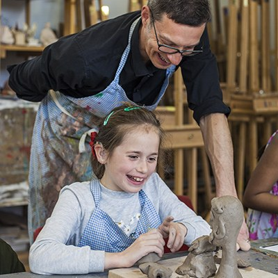 A child building sculptures in clay as a tutor looks over