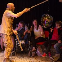 A bubble artist entertaining the crowd of vulnerable people
