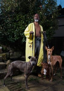 a man in a yellow long coat and no shirt, with chain mail trousers holding 3 dogs' leads