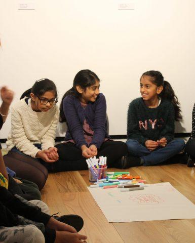 a group of school children sat down around some paper