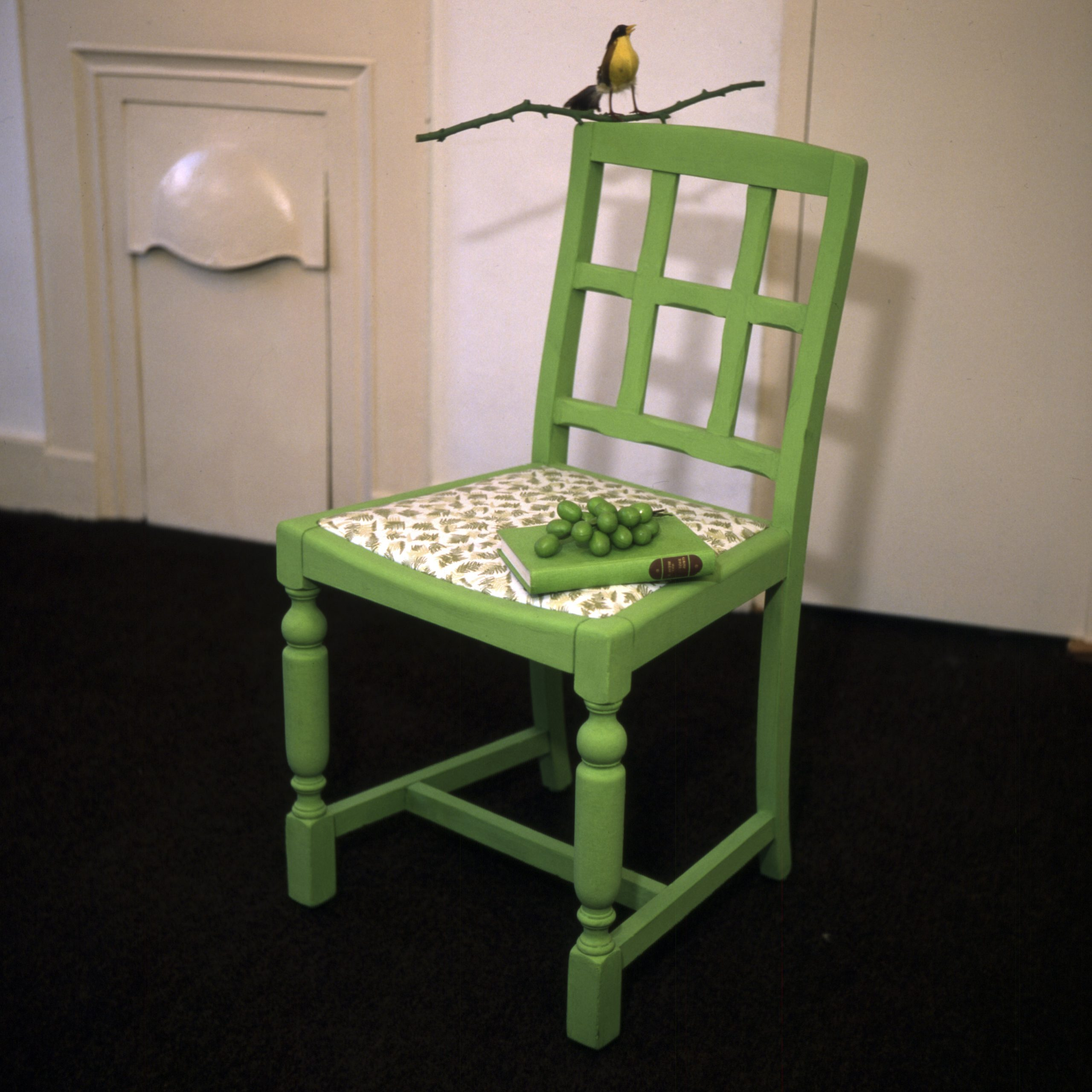 a green chair with a bird perched