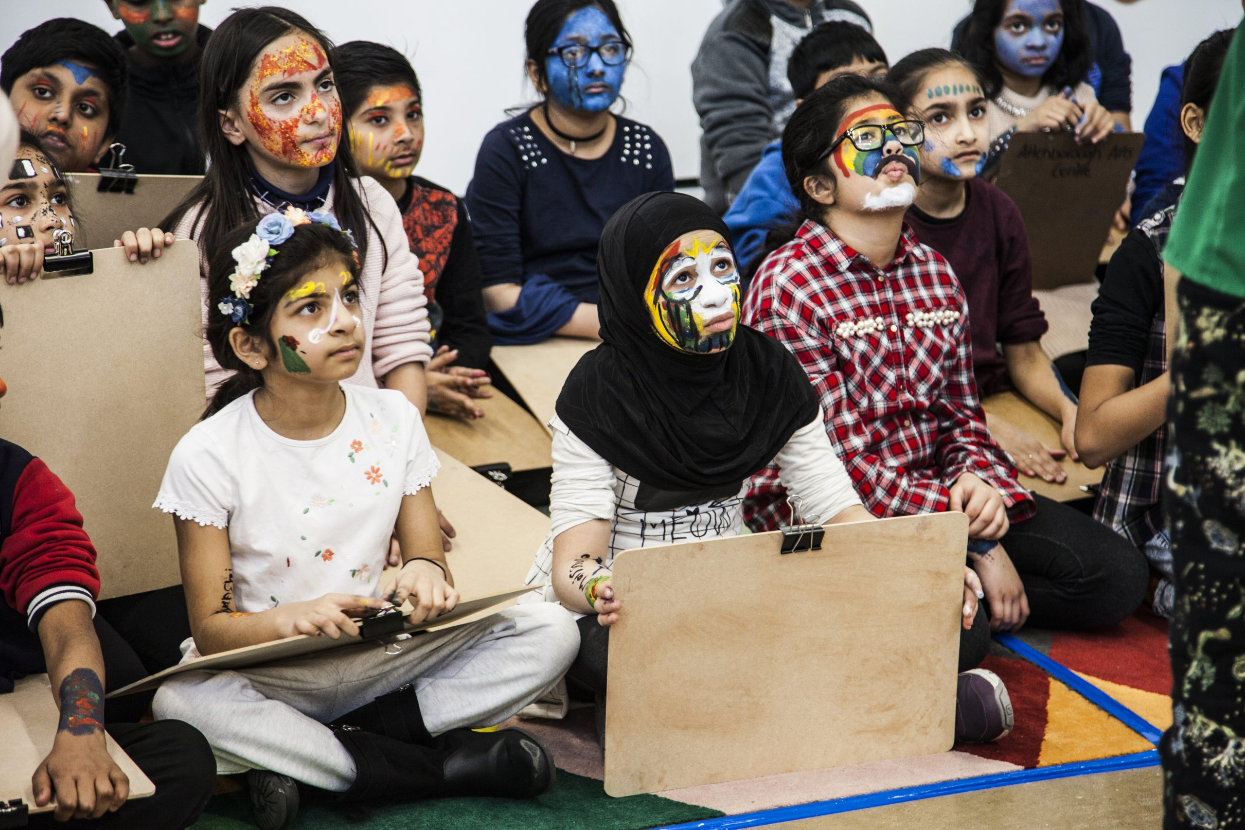 A group of young children with bright painted faces