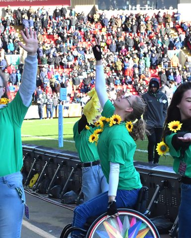 Dancers in green t-shirts holding sunflowers, in front of the crowd at Welford Road