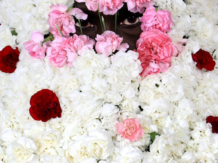 A man's eyes peep through a full flower bouquet