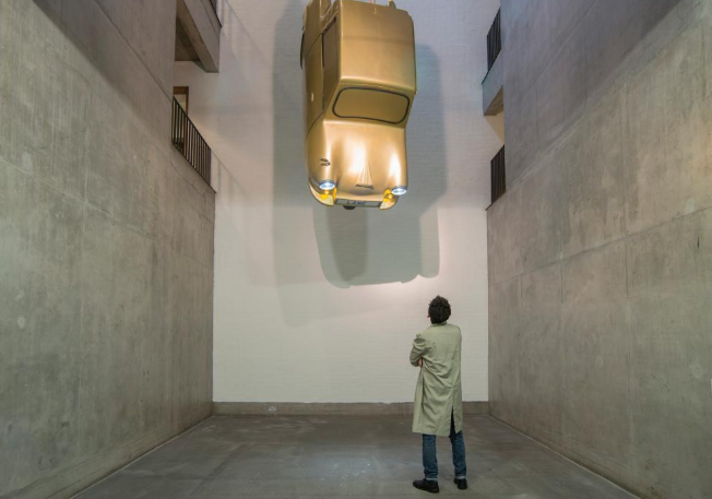 A small car hanging from the ceiling as a man looks on