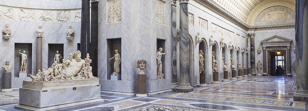 a large space, marble floor, with marble statues along the walls