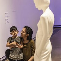 a young girl and her mum looking at a marble statue