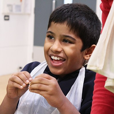 a child smiling wearing a plastic apron