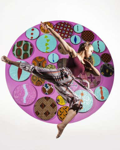 A dancer jumps, posing in front of a bright piece of art