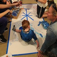 a child on a floor canvas painting with his hands