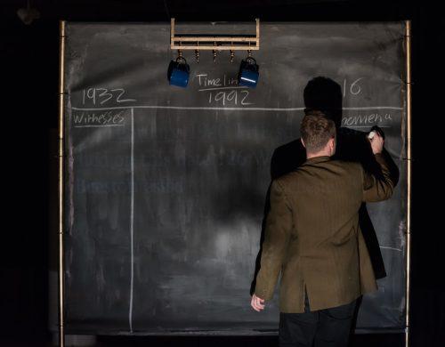 a man in a brown blazer writes on a chalk board
