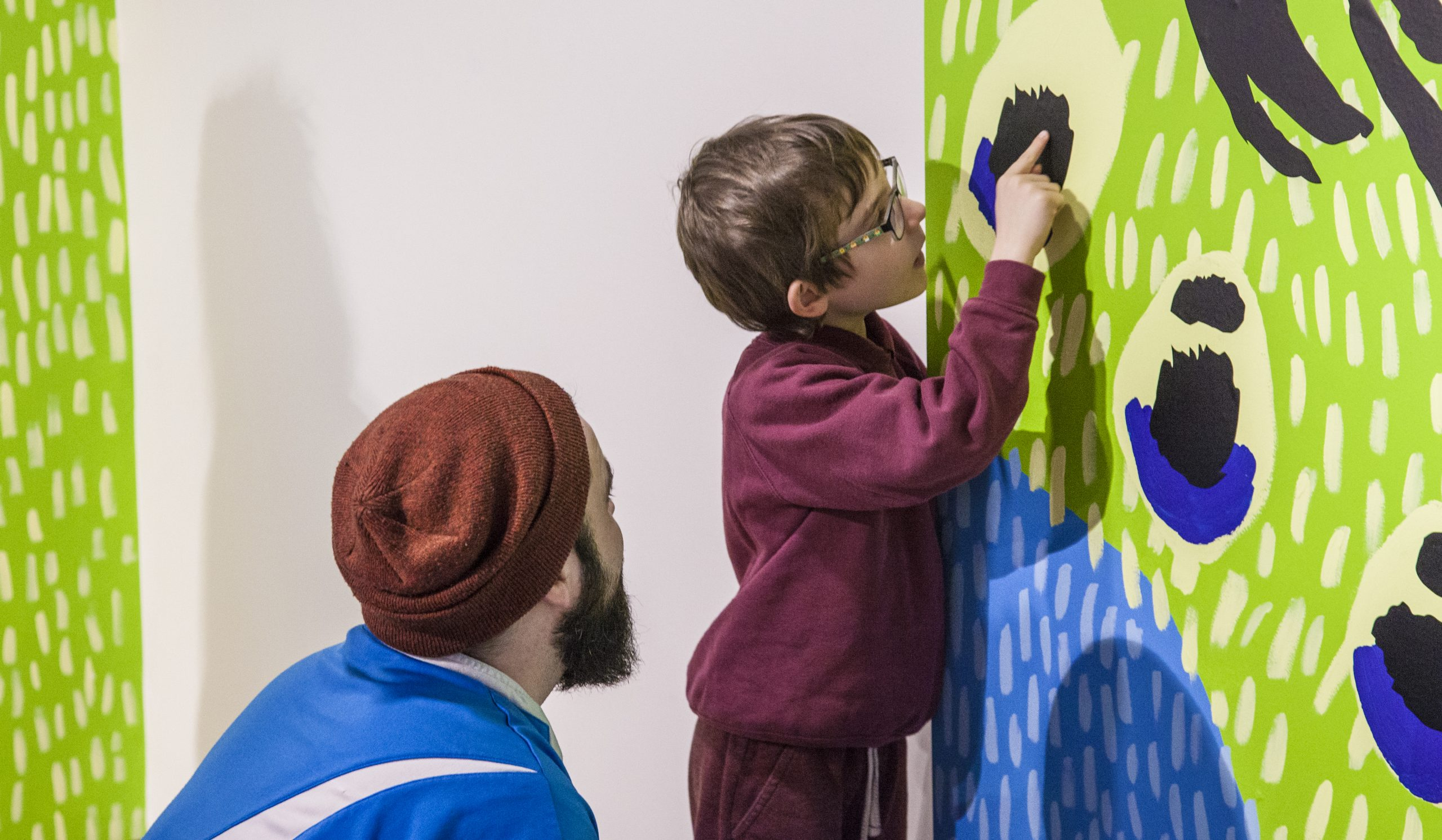 a child touching art on the wall, engrossed