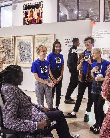 Group of young adult artists talking to an artist