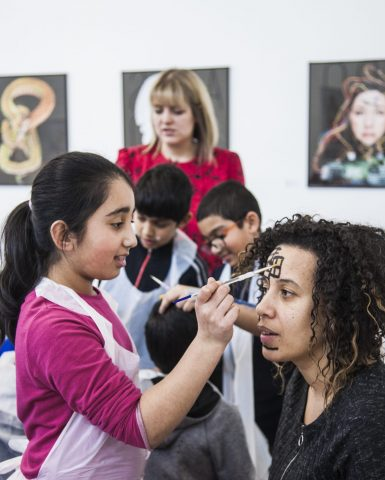 a child painting an adult's face