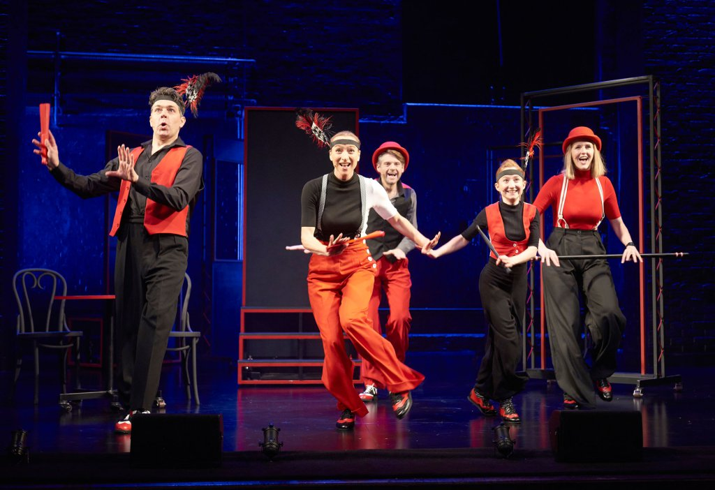 5 people in black and red dancing on stage
