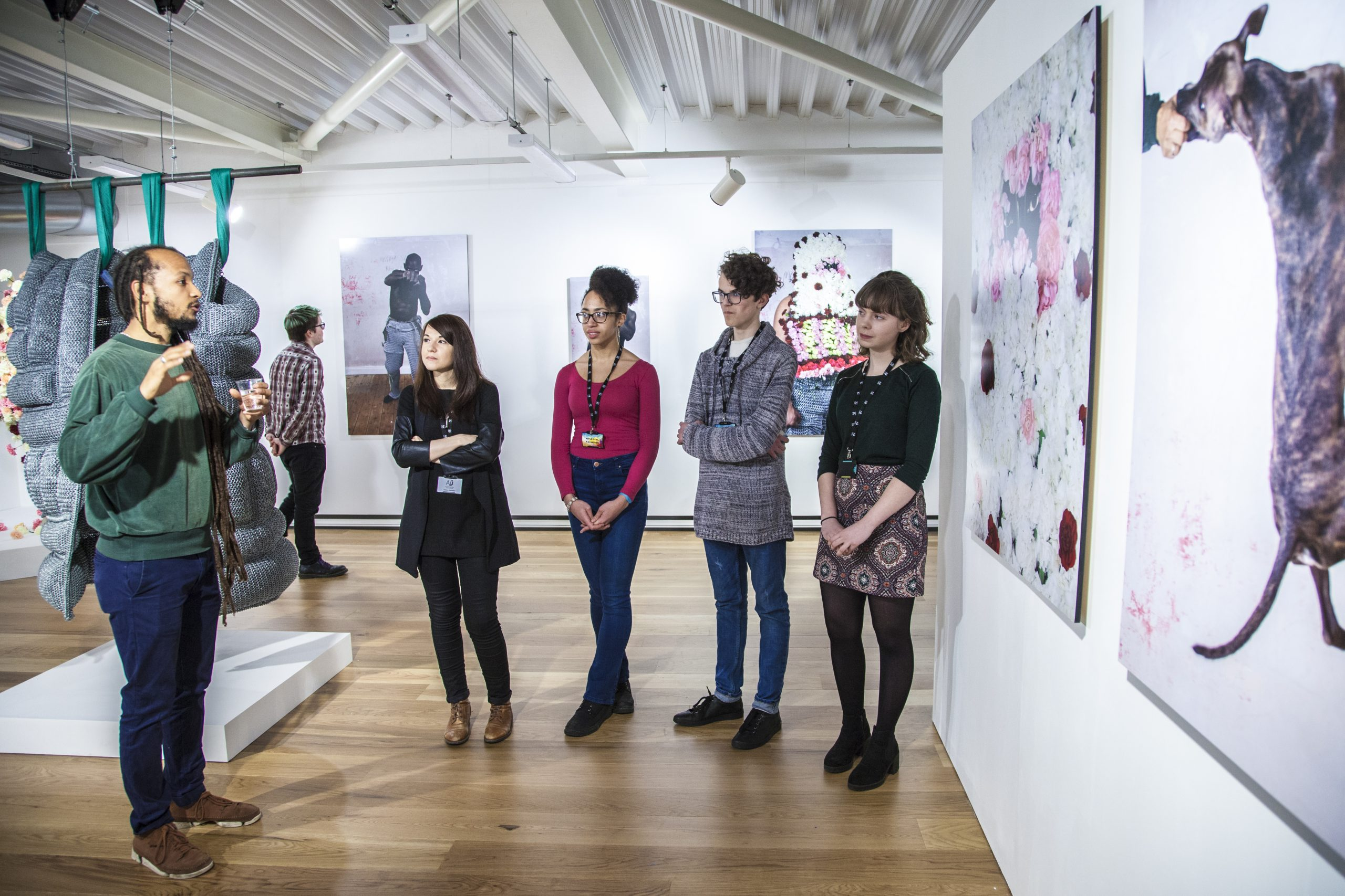 four young adults are listening to a man talk about the art covering gallery walls