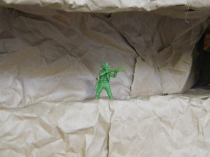 a green army man toy in a cave