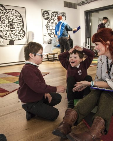 two children sat with a smiling education practitioner in the gallery