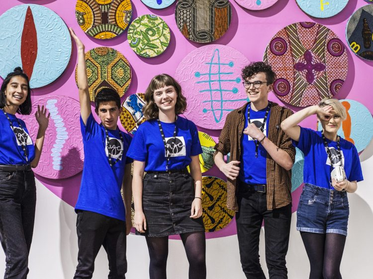5 young adults in blue shirts posing in front of a large, pink artwork