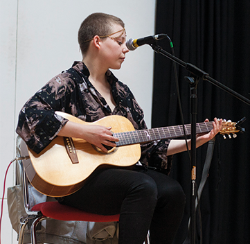 a woman on a chair playing an acoustic guitar