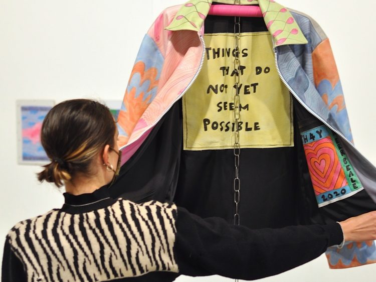 A woman opening a designer jacket. Text: Things that do not yet seem possible