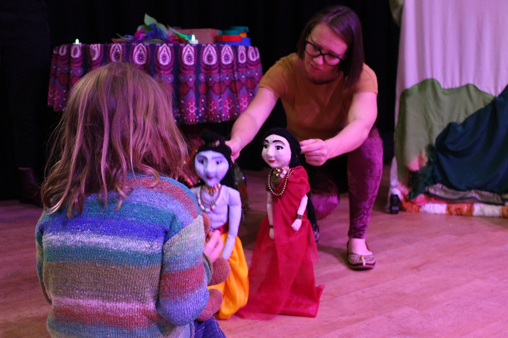 A Diwali family extravaganza event where a child is being shown two held up puppets representing Vedic God Lord Rama and Goddess Sita Devi.