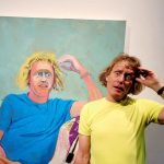 Grayson Perry standing, posing in front of his own portrait by artists Lucy Jones