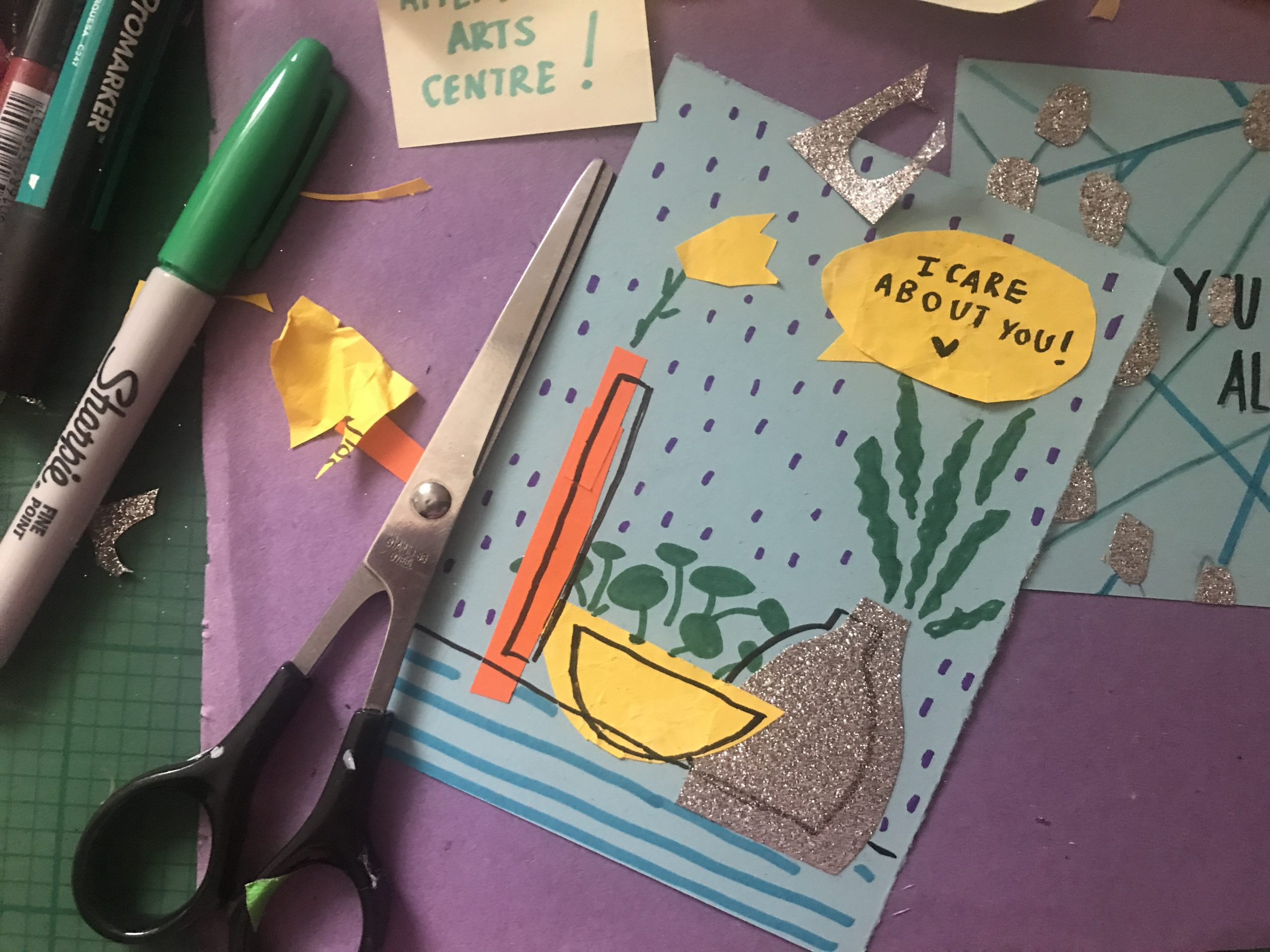 A photo of an artist's desk shows two postcard designs on blue card. The one on the left is a portrait collage of three flower vases in the rain, saying 'I care about you'. The one on the right is landscape and reads 'you are not alone', with all the Os connected to a web of silver circles surrounding the words. In the background is a purple sheet of paper on a green cutting board, surrounded by pens, Soofiya's rainbow business cards and yellow post-it-notes