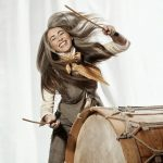 Dame Evelyn Glennie holding a stick in each hand about to hit a large drum with her hair lively swaying with a big smile on her face