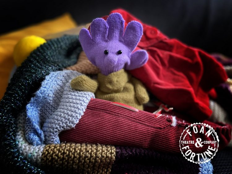 A pile of woolens, with a happy purple faced teddy in the middle