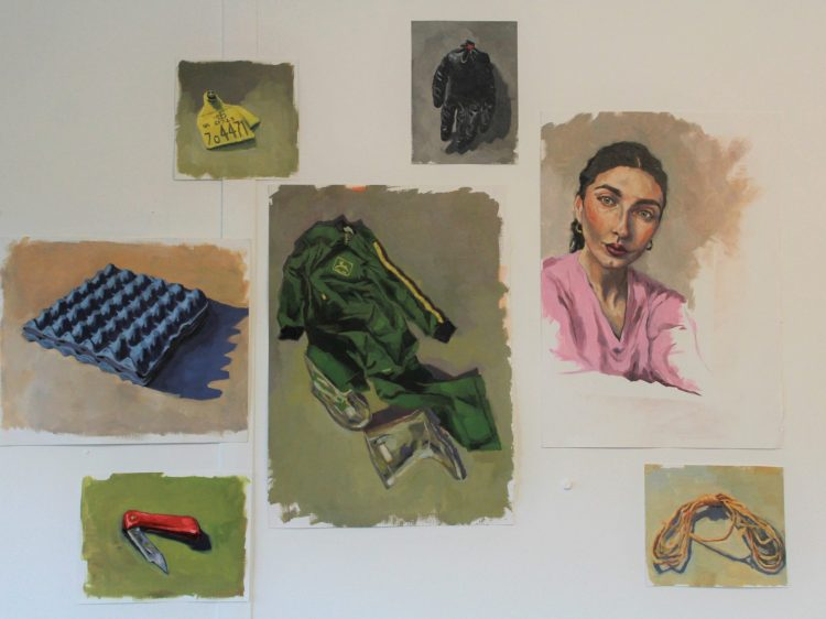 Photograph of seven oil paintings stuck to a plain white wall. The paintings are painted on sheets of white paper, all varying in size. The centre painting features a pair of overalls and wellies, the surrounding paintings feature a portrait, some rope, a penknife, a blue egg carton, a yellow tag and a black glove.