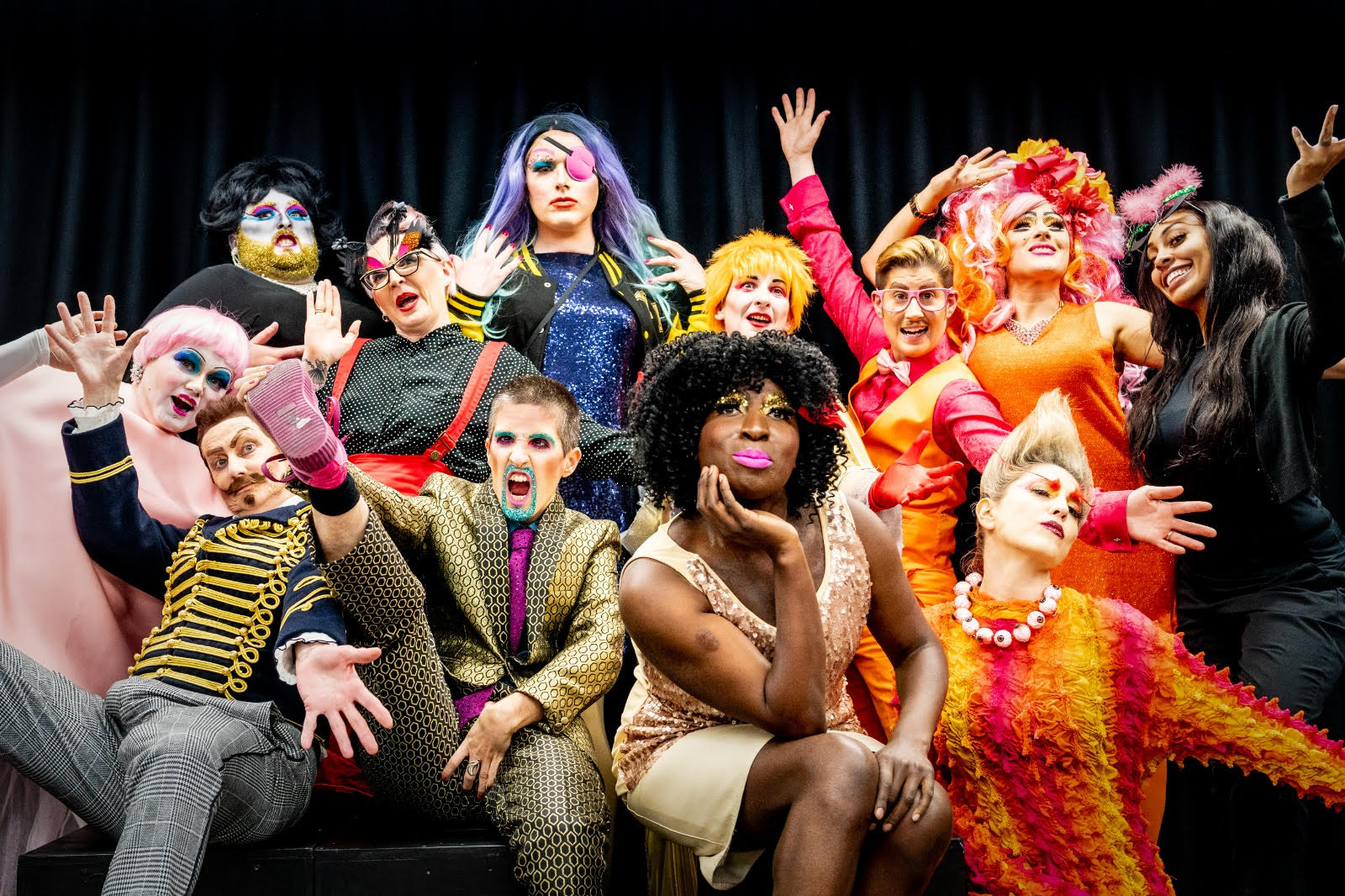 A large group of brightly coloured performers, in bright glittery make up