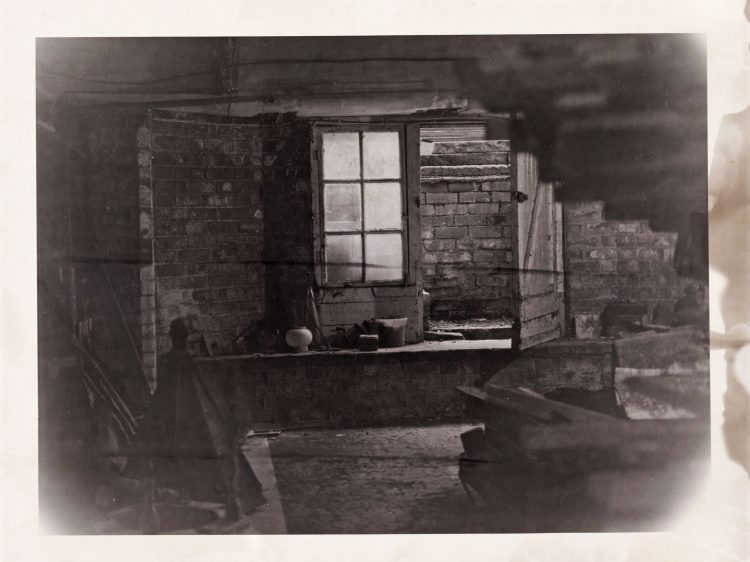 Black and white photograph of a basement. The image fades towards the edges, surrounded by a smudged white boarder. A dusty six-pane window lights up the centre of the photograph on the far wall. The walls are exposed brick. Household items and piles of wood clutter the basement, blurred in the foreground.