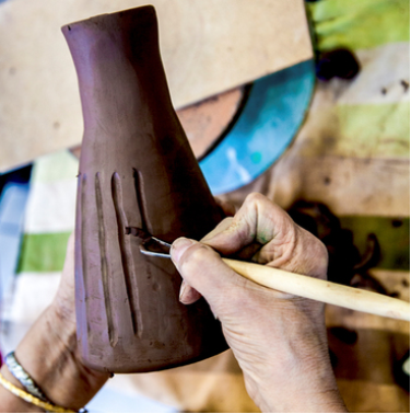 A woman carving lines into a clay pot