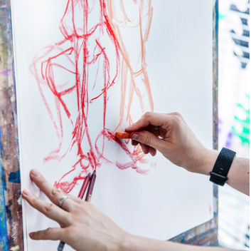 Pair of hands drawing human forms on an easle