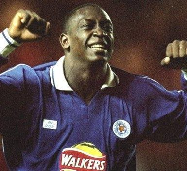 Emile Heskey in a Leicester City kit, arms raised