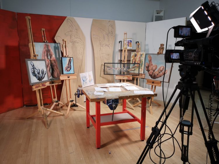 A setting of an art studio with a camera filming