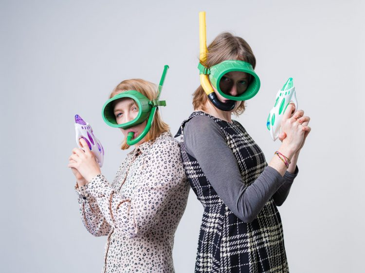 Two women, back to back, holding water pistols and with snorkels in their mouths