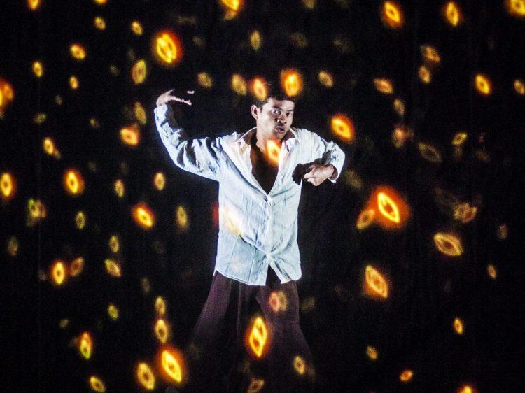 a man dancing in amongst orange lights floating about him