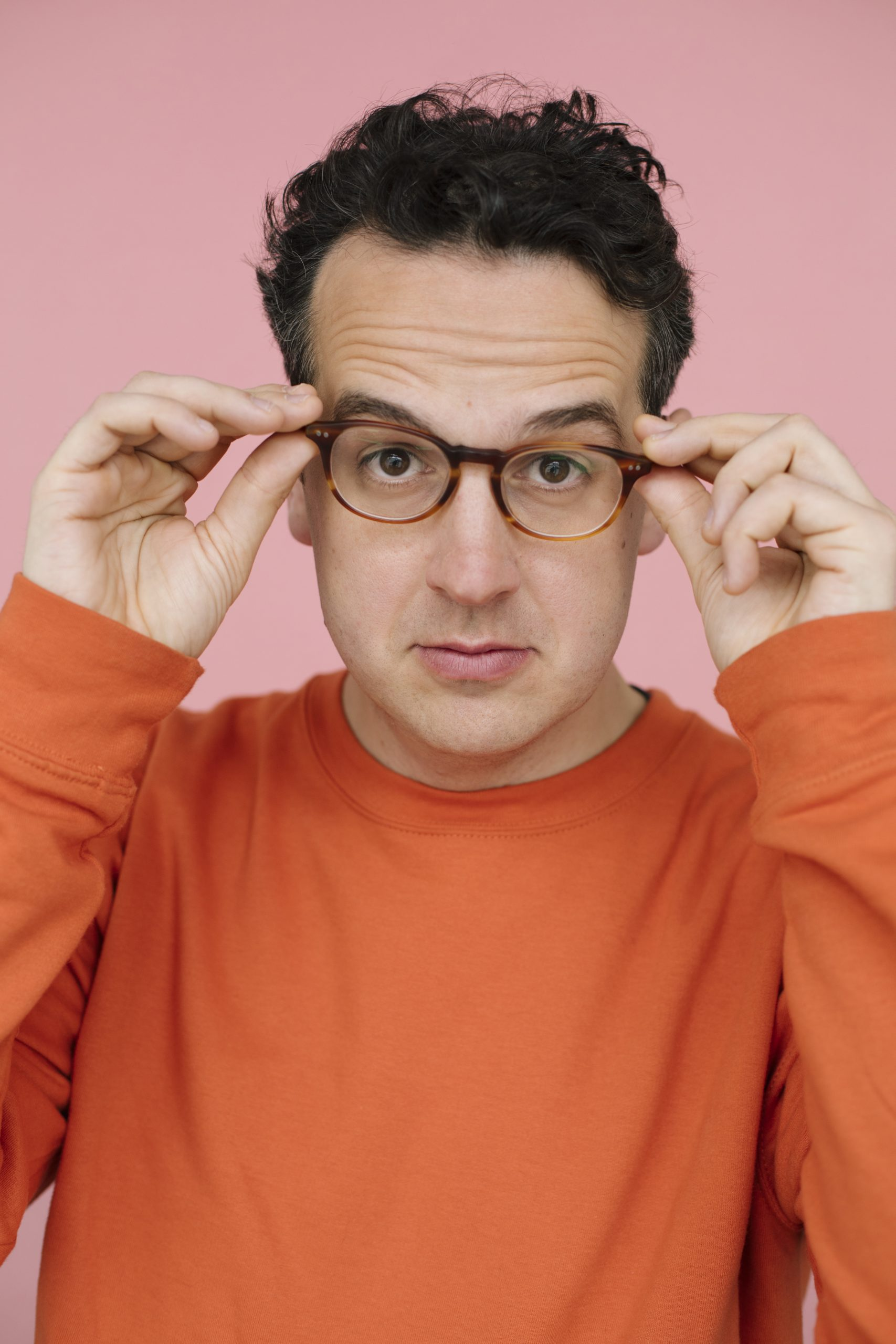 a man with glasses, posing