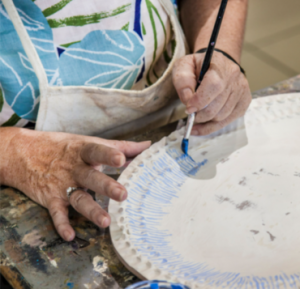 A person drawing on a ceramic plate